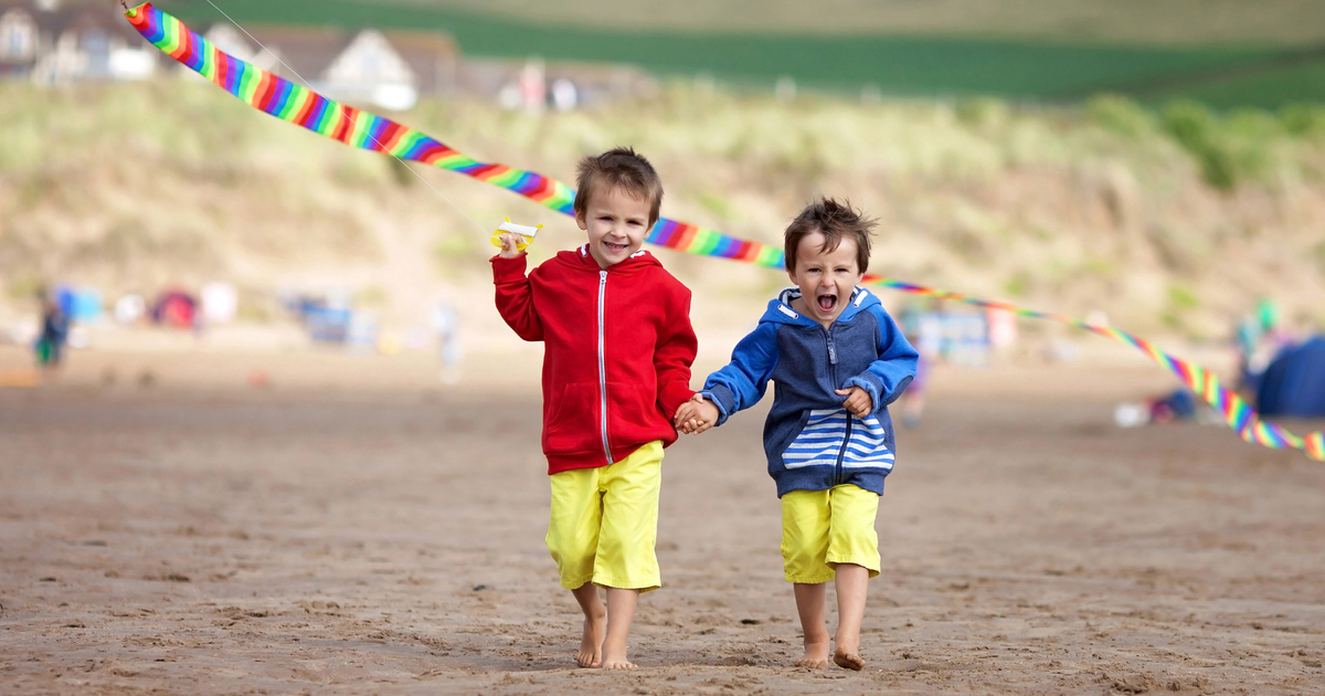 boys enjoying a staycation on an english beach flying a kite