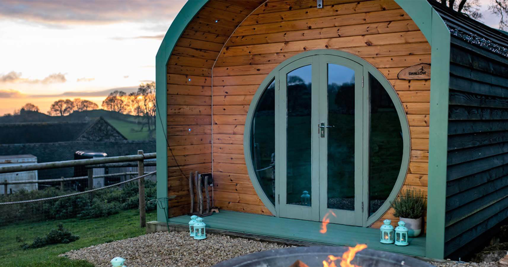 A wooden glamping pod with fields in the distance