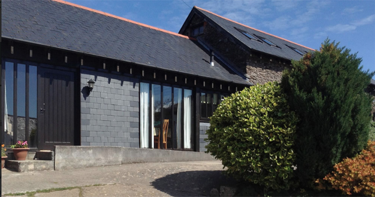 a grey-brick cottage with black slate roof