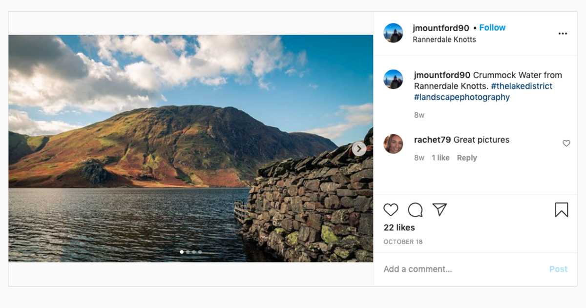 Instagram screenshot showing a stone wall jutting in to a lake with a heath-covered hill rising in the distance under a blue sky