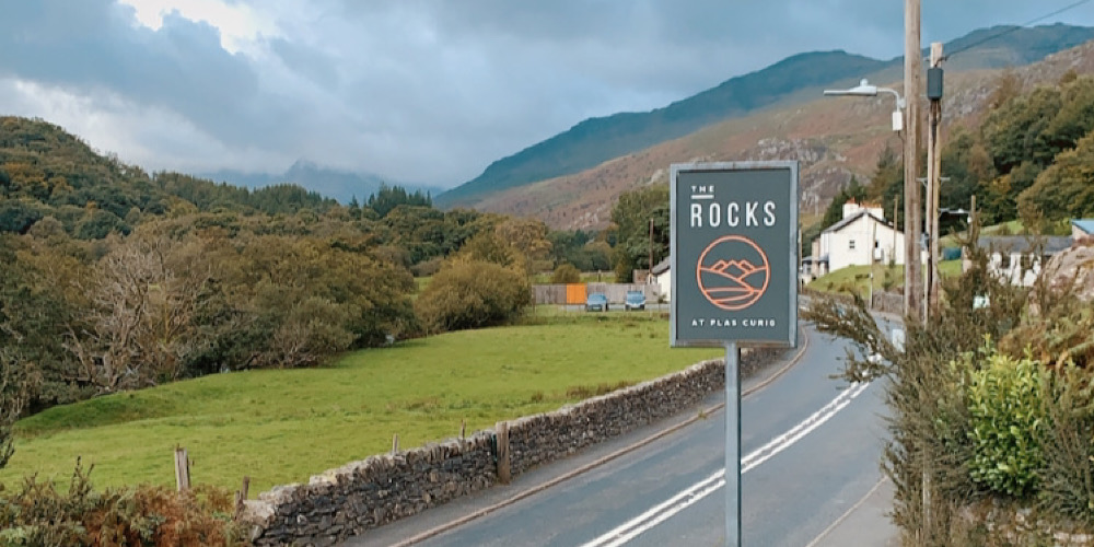 The Rocks Hostel at Plas Curig sign with Snowdon range in The Background